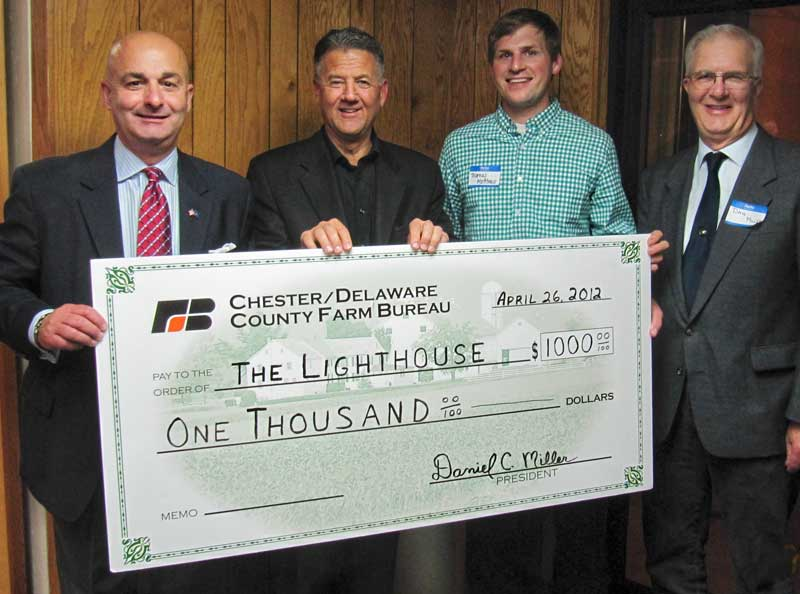 Joe Fecondo, the local Farm Bureau's vice president (from left); Ed Herr, president of Herr's; Thomas Matthews, a Farm Bureau board member; and Dan Miller, the bureau's board president, display a donation check for the Lighthouse in Oxford.