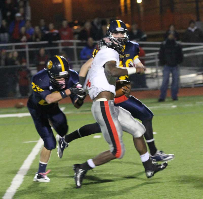 Coatesville Worley breaks away from Unionville defenders, Friday night. Worley's 228 yards rushing led the red Raiders to a PIAA District One playoff win over the Indians, 38-21. Jim Gill photo.