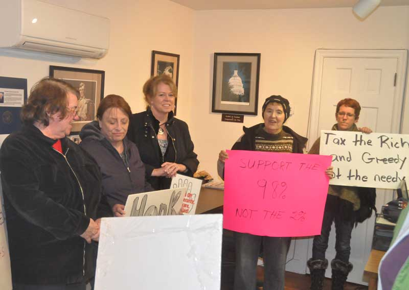 Local residents gather to sing satirical Christmas carols and talk spending and taxes in the district office of U.S. Rep. Joe Pitts in Unionville, Monday evening. The local group, organized in part by MoveOn.com and the Kennett Area Democrats, was one of more than a hundred similar such gatherings at district offices around the country.