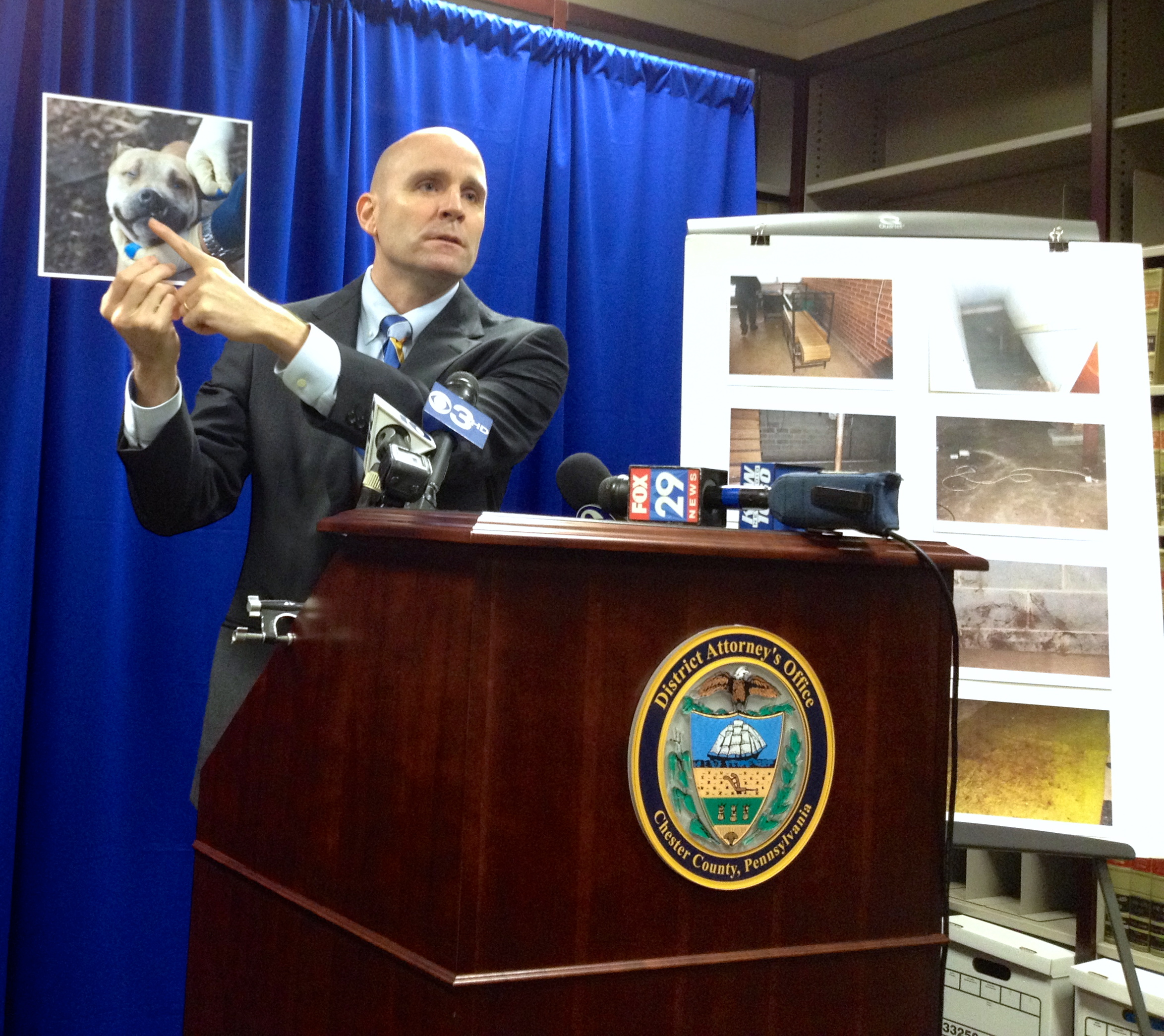 Chester County District Attorney Tom Hogan displays disturbing photos taken at a West Brandywine Township residence, where a couple allegedly ran a dog-fighting ring