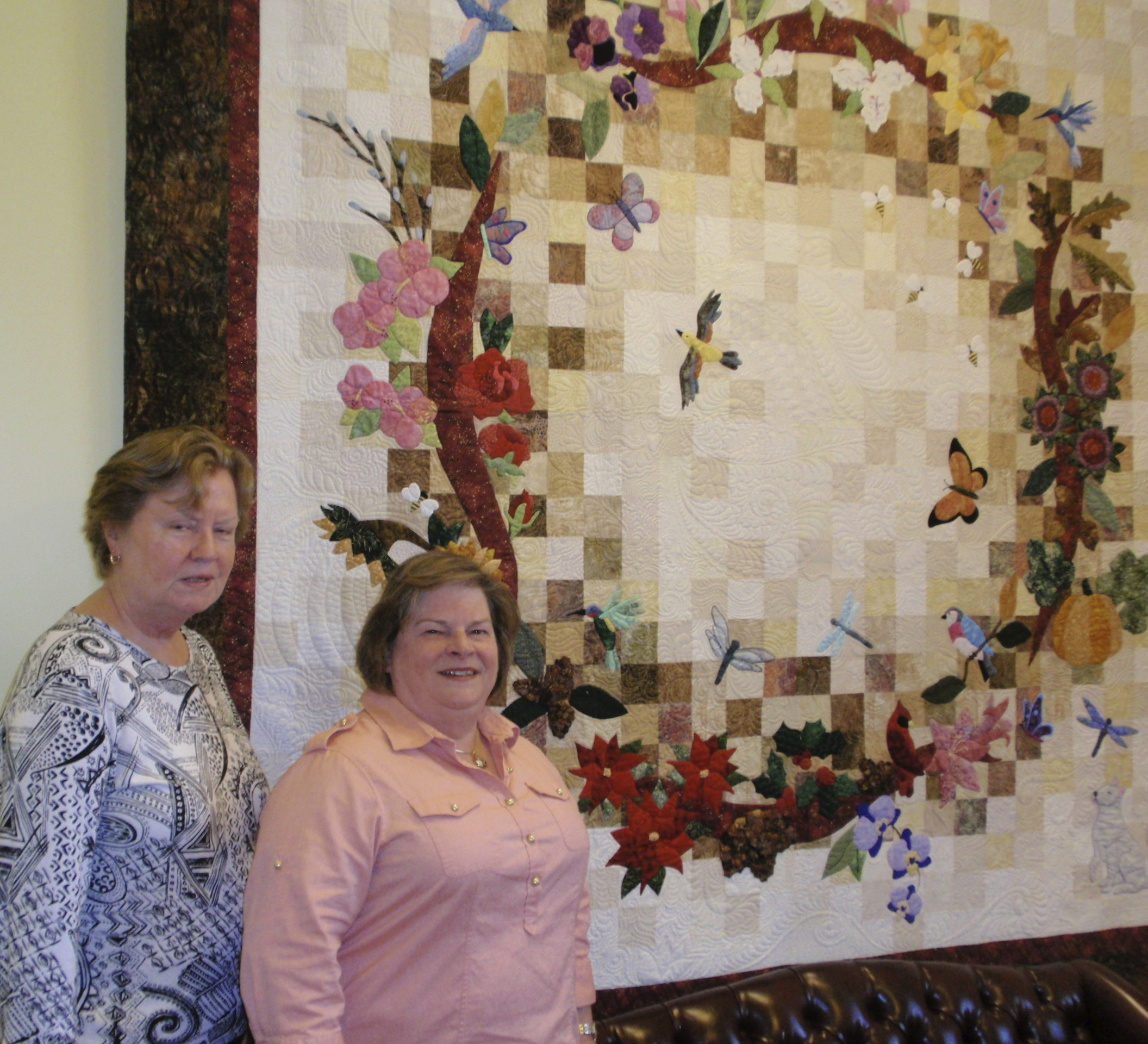 """Ann Randolph (left) and Nancy Hiss stand in front of the group's """"Seasons of Pollination"""" quilt."""