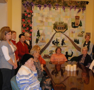 Members of Longwood Gardens volunteer quilting group listen to the rave reviews the quilts have garnered at the Brandywine Valley Tourism Information Center. Behind them is a quilt inspired by Longwoods sounds.