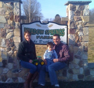 Jamie Hicks (from left) sits with his son, Graham, and wife Kate at the entrance to Meadow Springs Farm on East Doe Run Road.