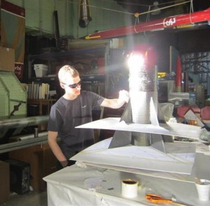 Jason Silverman works in a USC  lab under bright lights that help cure the epoxy that is applied to the rocket.