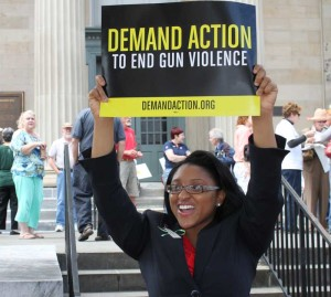 A supporter of universal background checks for gun purchases holds her sign at a rally, Friday, to commemorate the six-month anniversary of the school shootings in Newtown Square, Connecticut. The event, one of many across the state was organized by Mayors Against Illegal Guns and local community groups.