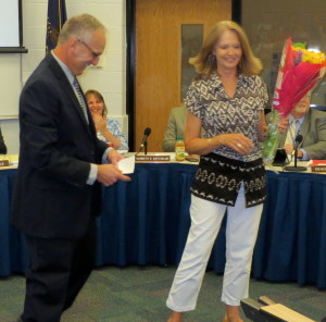 Linda Feathers, who retired as a technology support specialist at Hillendale Elementary, receives flowers from Principal Steve Dissinger.