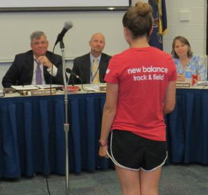 Board member Victor Dupuis (from left), Superintendent John Sanville, and board member Holly Manzone listen as Unionville track star Olivia Young explains why the  team needs more coaching support.