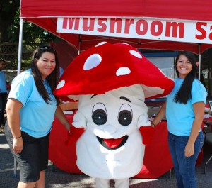 Two volunteers share a moment with Fun Gus, the official mascot of The Mushroom festival, during the 2012 event.