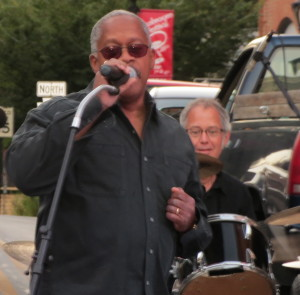 "Borough Councilman Leon Spencer, a member of the band Good Foot, urges the crowd to have a ""good, good night"" at the post-parade festivities of the Mushroom Festival."