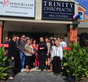 Dr. Joey Gaglioti (front, holding scissors) celebrates the Trinity Chiropractic ribbon-cutting with clients, guests, family and friends.