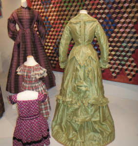 Two women's dresses, a  green striped silk and a purple and black plaid silk taffeta, and two child's dresses, a red, black and white plaid cotton and a magenta, black and white plaid wool with black velvet trim, were worn in Chester County in the 1860s and 1870s.  from 1869-1872