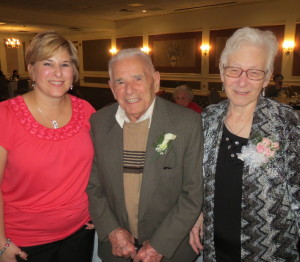 Enjoying his 100th birthday party, Mike DiPietro is flanked by his daughter, Lisa, and his wife, Teresa.