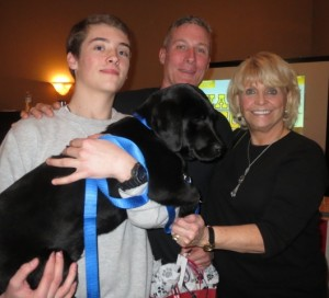 "Chester County Sheriff Carolyn ""Bunny"" Welsh poses with the winner's of the black Lab, which came from Cedar Creek Farm in Nottingham: Jake Read (from left), and his father, Matthew Read. The pair said they purchased the puppy for Jake's grandmother."