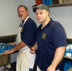 Sheriff Deputies Dave Reeves (left) and Ben Tobin display their dish-washing prowess in the kitchen.