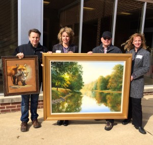 Displaying two of the oil paintings for the 65th Annual Chadds Ford Art Sale and Show are artist Shawn Faust (from left), co-chair Frances Galvin, artist J. Wayne Bystrom, and co-chair Lynda Nadin.