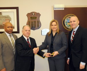 New Chester County Detective Kristin Lund is congratulated by Lt. Kevin Dykes (from left), Chief Detective James Vito, and District Attorney Tom Hogan.
