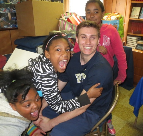 Fifth-grade Study Buddies participants Johnnette Boddy (from left), Jalayshia Allen and Aalana Vasquez gleefully surround their helper, Unionville High senior Clark Bingol.