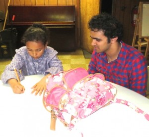 Unionville High junior Abu Akki oversees the work of 6-year-old Payton Myers-Corp during the Study Buddies after-school program.