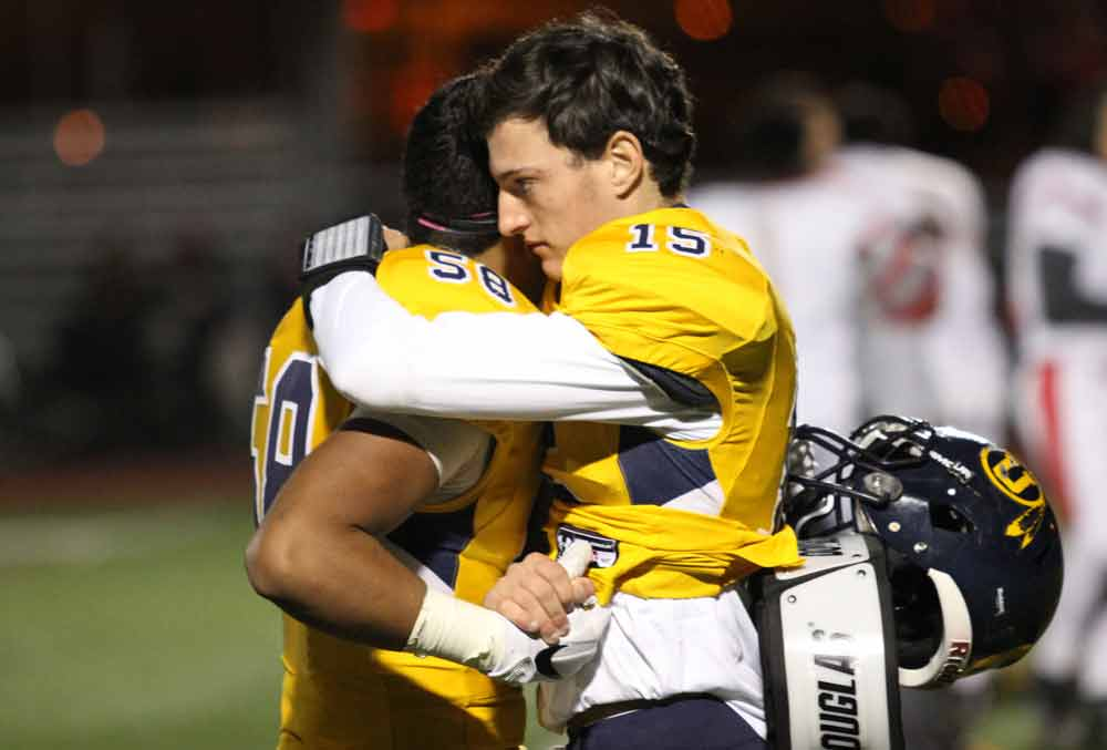 Unionville's Alex Gorgone shares a hug with teammate Pablo Aviles-Bernal following Friday's loss to West Chester East. Jim Gill photo.