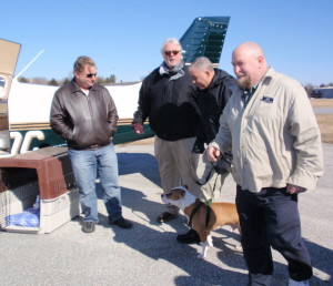 Pilot Matt Kiener (from left), Chester County SPCA spokesman Rich Britton, Chester County SPCA Animal Protective Services Officer Craig Baxter and Chester County SPCA Operations Manager Mike Dempsey get ready to put Radar in his crate for the plane ride.