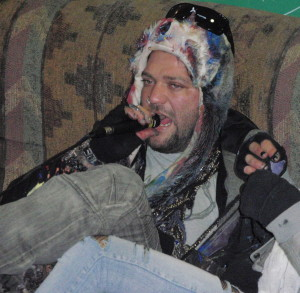 Bam Margera sits on a couch and belts out vocals during a jam session at his art show Tuesday night.