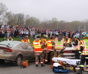First-responders work to extricate the students trapped in the vehicle during  the mock crash exercise.