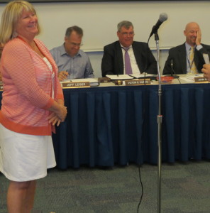 Sue Natale, who retired as an assistant in the district's technology department, listens as Josh Boughner, the network administrator, discusses the ways in which she will be missed.