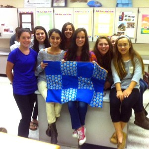 It's finished! Patton students (left to right) Rebecca Peakes, Taryn Thompson, Leah Narun, Sophia Kolliopoulos, Helen Nichols, Lara Jensen, Ariana Birney, and Natalie Pechin proudly show off their completed quilt as part of the Patton Project. The quilt will be given to a child at A.I. duPont Hospital for Children.