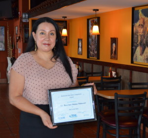 Josefina Nino of El Ranchero Mexican Restaurant shows off the certificate the eatery received in the salsa competition.