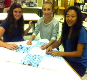 Patton students (left to right) Madyson McDougal, Rachel Ioele, and Cara Freedman work on a quilt to be donated to sick children at A.I. duPont Hospital.