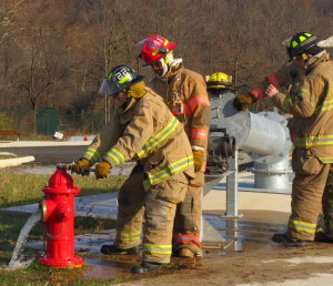 As her colleagues watch, Hayleigh Hunter, 17, of Avon Grove High, drains the fire hydrant so that the hose can be attached.