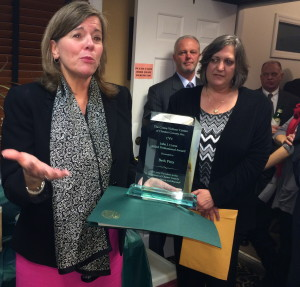 "Elizabeth B. Pitts (left) explains why the 2013 John J. Crane Award means so much to her as attorney Dawson R ""Rich"" Muth, County Commissoner Kathi Cozzone, and Chief County Detective James Vito look on."