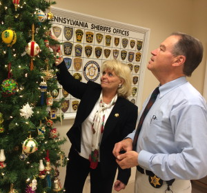 "Chester County Sheriff Carolyn ""Bunny"" Welsh and Chief Deputy Sheriff George P. March scan the tree for their favorite ornaments from a collection handcrafted by March's mother, Alice March, who died in September."