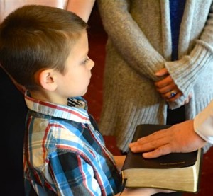Jay Suydam holds the Bible as his father, Jason Suydam, is promoted to lieutenant in the Chester County Sheriff's Office.