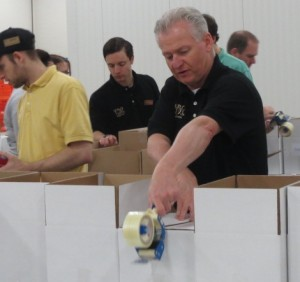 Wegmans Malvern Store Manager Jerry Shelly demonstrates his taping skills during the sorting of more than 18,000 pounds of food donated by his company.