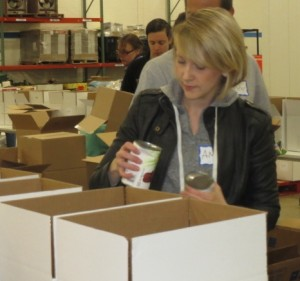 Amy Strauss from the Town Dish checks the expiration date on one of the hundreds of cans that needed to be sorted.