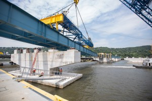 The I Lift NY super crane places an immense steel girder assembly on the new bridge's concrete piers.