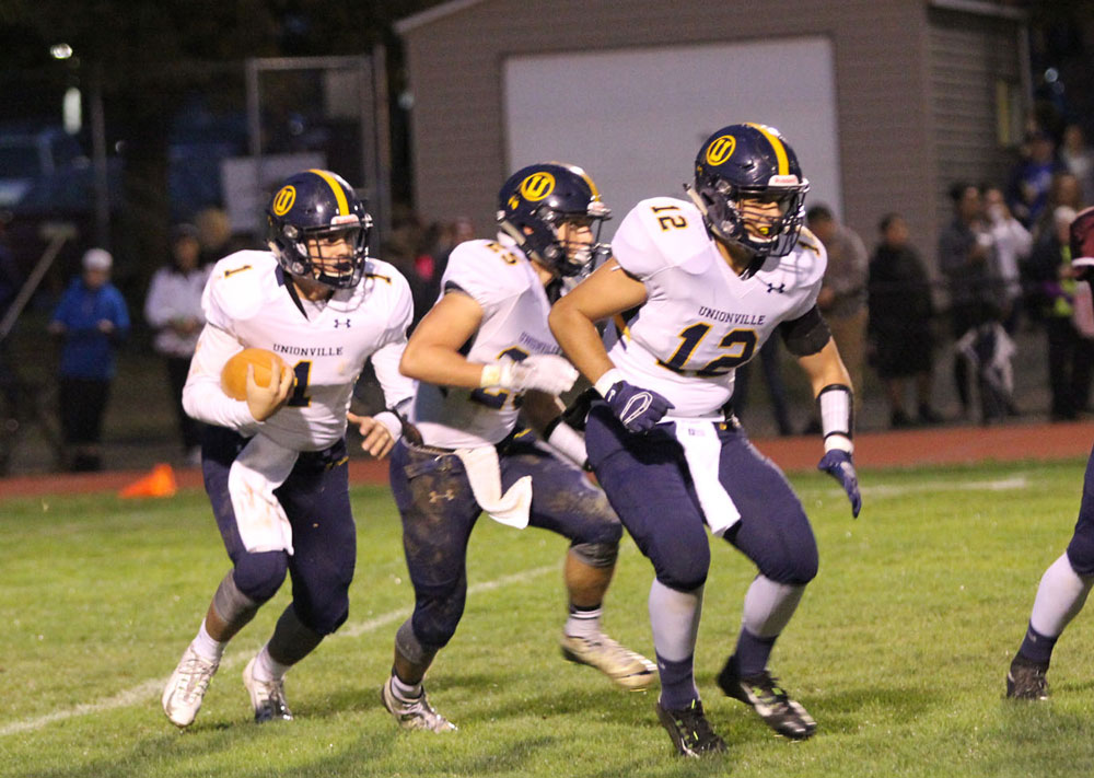 Unionville quarterback Joe zubillaga looks for running room behind Jack Adams (25) and chris D'Amico (12). Jim Gill photo.