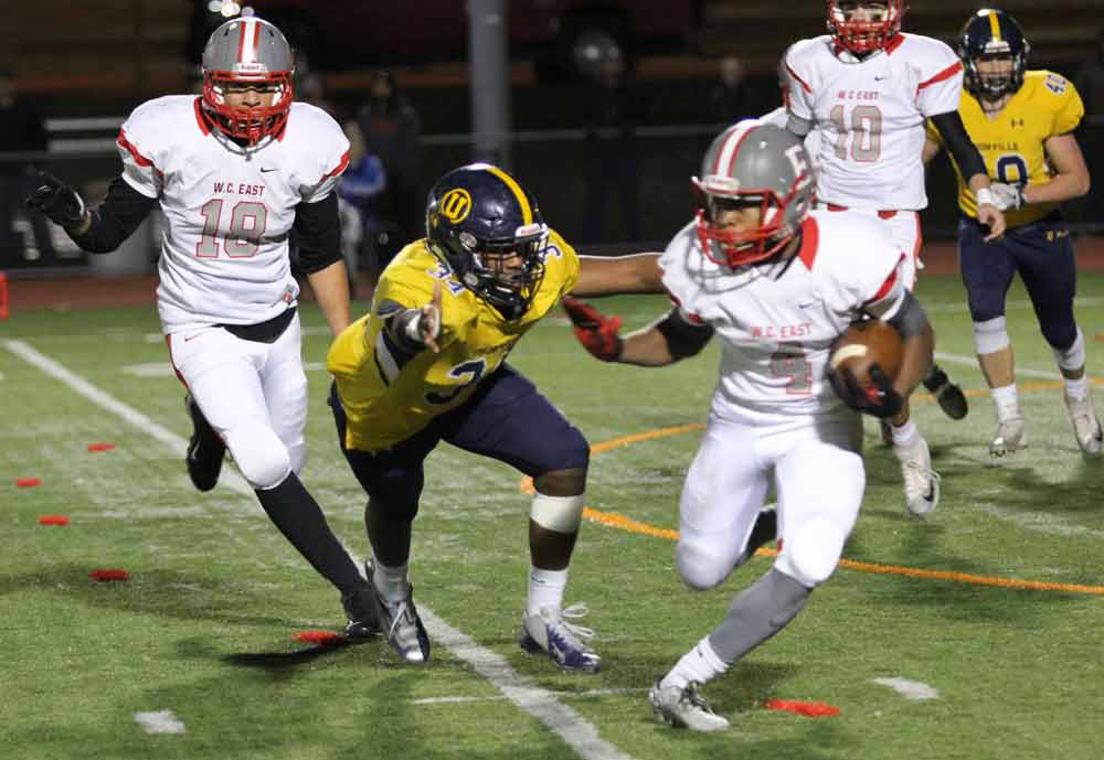 Unionville's Bryce McManus closes in on West Chester East's Jared Cooper. Jim Gill photo.